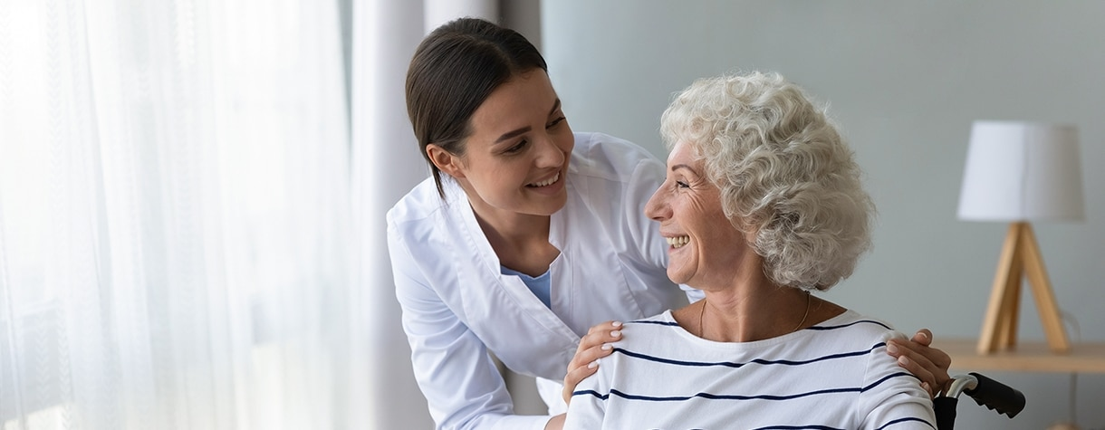 Smiling disabled elderly woman in wheelchair talking with caring nurse